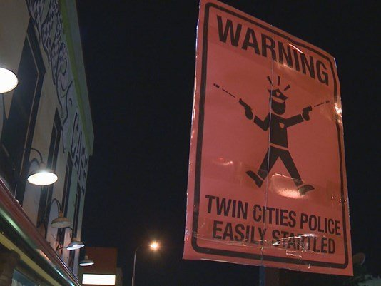 """© Credit : KARE   The signs, which read """"Warning: Twin Cities Police easily startled"""", appeared at least twice on posts in Minneapolis and St. Paul over the weekend. This one was seen in the Cedar-Riverside neighborhood."""