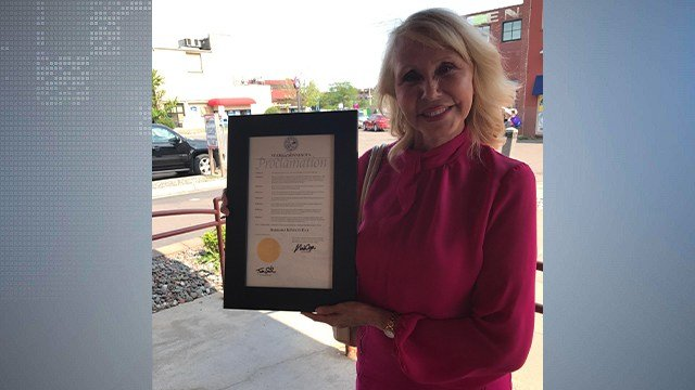 © Barbara Reyelts poses with the proclamation given by Governor Mark Dayton.